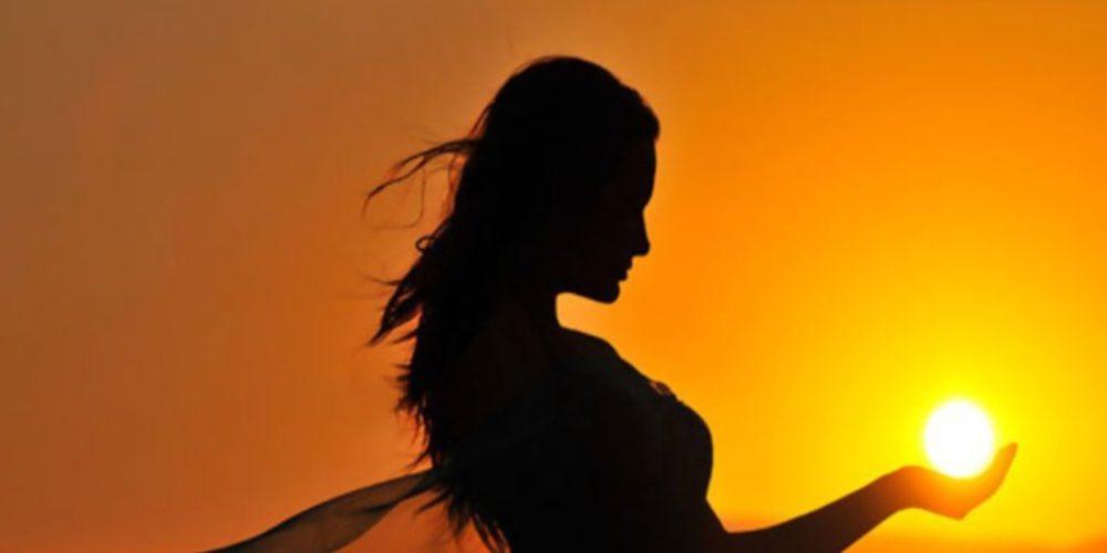 chica agarrando el sol con sus manos-977654